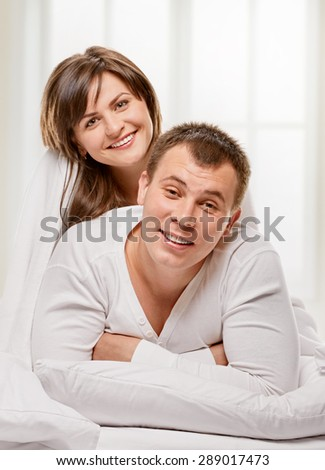 Happy smiling couple laying laughing in bed with light window background