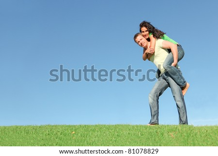 happy smiling couple outside on grass giving piggy back in summer - stock photo