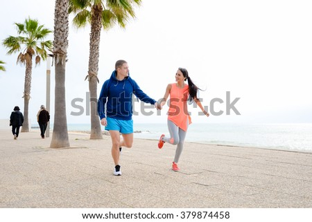 Happy smiling couple over palm trees beach background. Running lovers on vacation - stock photo