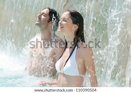 Happy smiling couple refresh under fresh waterfall at summer swimming pool