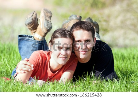 Happy smiling couple relaxing on green grass. - stock photo