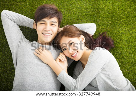 Happy Smiling Couple Relaxing on Green Grass - stock photo