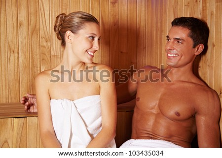 Happy smiling couple relaxing together in a spa sauna - stock photo