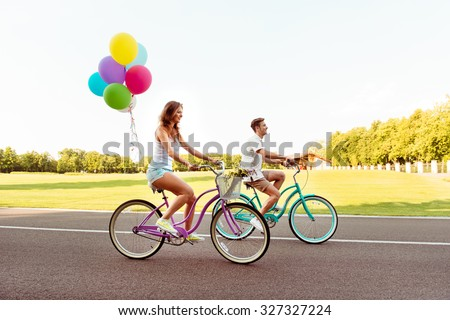 happy smiling couple ride bicycles have fun - stock photo