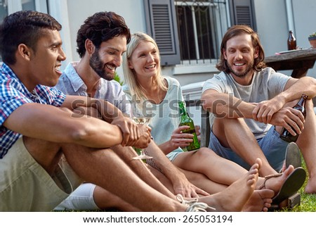 happy smiling diverse group of friends having outdoor garden party with beer wine drinks - stock photo