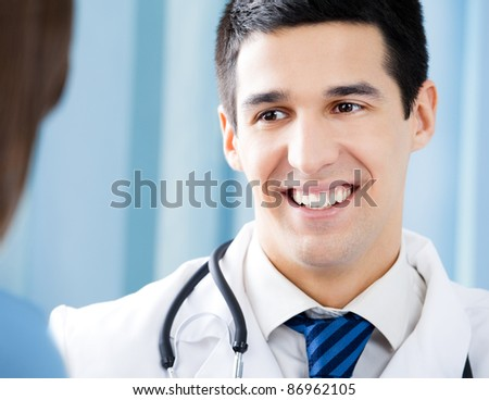 Happy smiling doctor and young female patient at office - stock photo