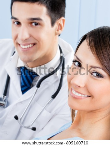 Happy smiling doctor and young female patient at office. Medicine and healthcare concept.