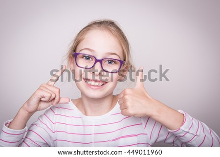 Happy smiling eight years old pretty blond caucasian child girl in violet glasses showing thumbs up gesture. Layout with free copy space. - stock photo