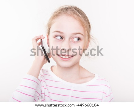 Happy smiling eight years old pretty blond caucasian child girl talking on mobile phone (smartphone). - stock photo