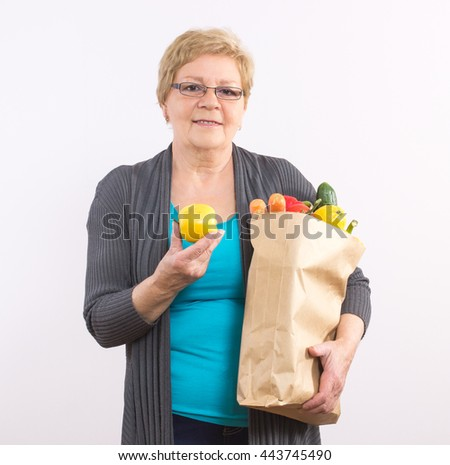 Happy smiling elderly senior woman holding fruits and vegetables in shopping bag, healthy nutrition in old age