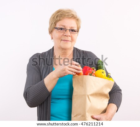 Happy smiling elderly senior woman holding shopping bag with fruits and vegetables, healthy nutrition in old age