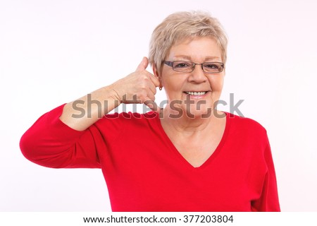 Happy smiling elderly senior woman showing sign shaped telephone, making call me gesture, positive human emotions, facial expressions