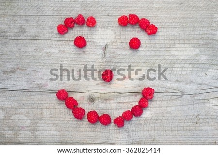 Happy smiling face made of fresh raspberries, top view - stock photo