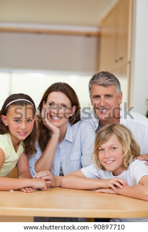 Happy smiling family behind kitchen table