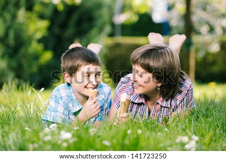 Happy smiling family eat ice cream on a grass outdoors in spring park - stock photo