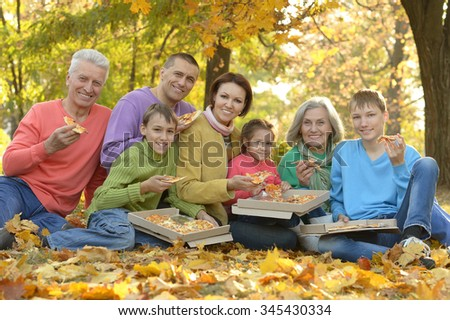Happy smiling family eating pizza in autumn park - stock photo
