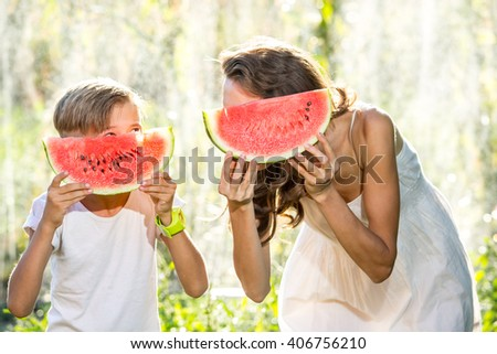 Happy smiling family eating watermelon on a sunny summer day, focus on hands - stock photo