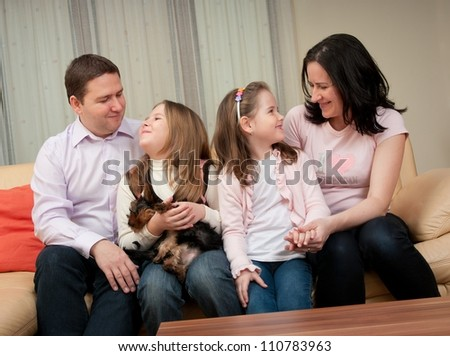 Happy smiling family enjoying together at home and dog