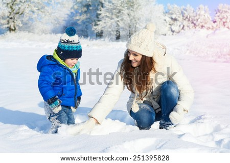Happy smiling family in snowy day - winter portrait of mother and baby boy - stock photo