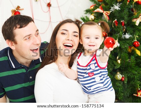 Happy smiling family near the Christmas tree - stock photo