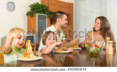 Happy smiling family of four eating with spaghetti at table. Focus on man