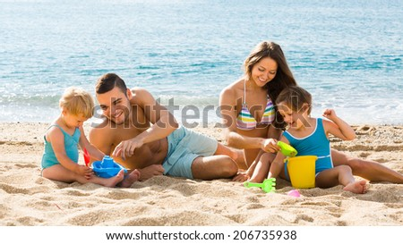 Happy smiling family of four playing with sand at beach in sunny day - stock photo