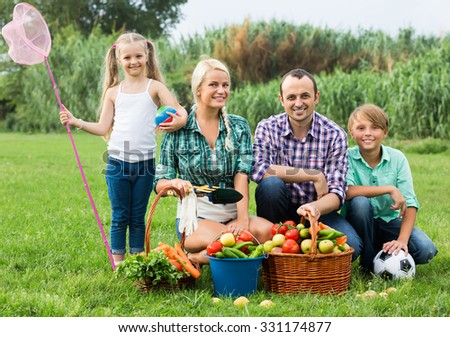 Happy smiling family of four resting at countryside at summer day