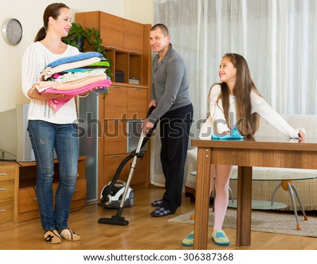 Happy smiling family of three cleaning in the living room all together - stock photo