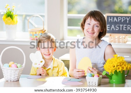 "happy smiling family of two enjoying easter time at home, doing crafts, little boy holding easter bunny shaped candy, easter themed decorations and blackboard sign ""happy easter!"" in the background"