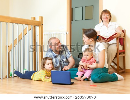 Happy smiling family of with blue computer on floor  - stock photo