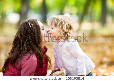 Happy smiling family playing against blurred autumn leaves background - stock photo