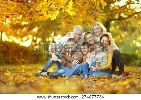 Happy smiling family sitting in autumn park - stock photo