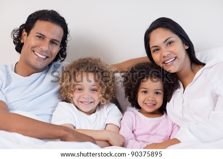 Happy smiling family sitting on the bed together