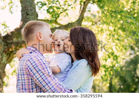 Happy smiling family spending time together with a tree on the background. - stock photo