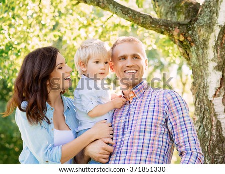Happy smiling family spending time together with a tree on the background.