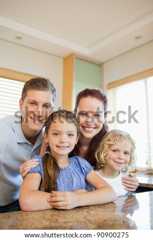 Happy smiling family standing behind the kitchen counter