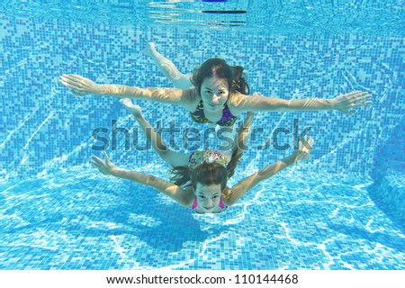 Happy smiling family underwater in swimming pool. Mother and child swim and having fun in water. Kids sport and fitness on family summer vacation. Active healthy holiday - stock photo