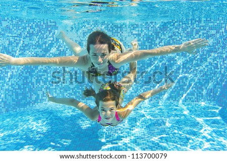 Happy smiling family underwater in swimming pool. Mother and child swim and having fun. Kids sport on family summer vacation. Active healthy holiday