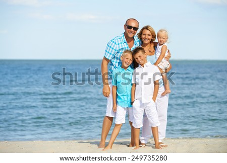 Happy smiling family with children standing on the sunny beach in full length. - stock photo