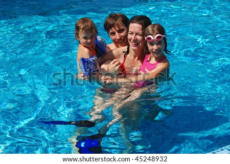 Happy smiling family with kids having fun in swimming pool - stock photo