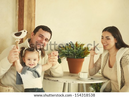 Happy smiling family with one year old baby girl drinking coffee indoor