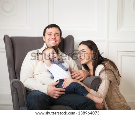 Happy smiling family with one year old baby girl indoor