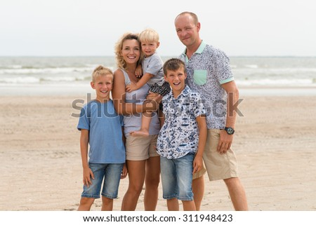 Happy smiling family with three children standing on the sunny beach.