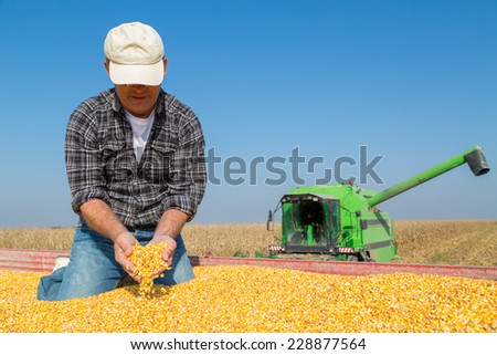 Happy smiling farmer during corn maize harvest - stock photo