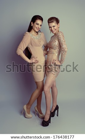 Happy smiling fashion girls in stylish diamond clothes posing in studio. Portrait of young attractive Caucasian people wearing expensive dresses.