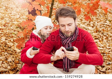 Happy smiling father and daughter looking at the mobile phone while sitting outdoor in an autumn park - enjoying modern technology - stock photo