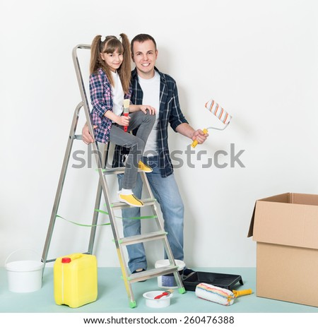 Happy smiling father and daughter makes repairs at home. - stock photo