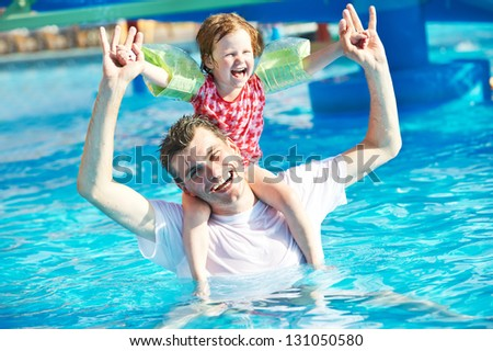 Happy smiling father man and child girl playing at water park in resort hotel swimming pool - stock photo