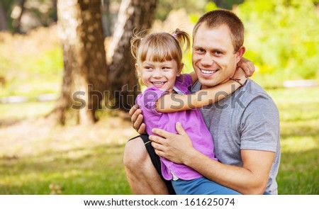 Happy smiling father with his little daughter  on hands - stock photo