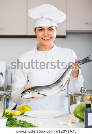 Happy smiling female cook in white uniform preparing big fish in restaurant